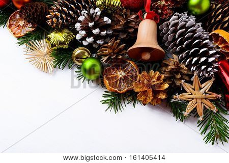 Christmas greeting background with handmade wooden jingle bell and pine cones. Christmas decoration with green ornaments and dried orange slices. Copy space.