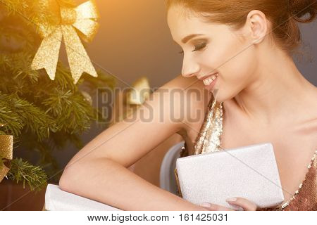 Portrait of young woman with christmas present boxes in front of christmas tree