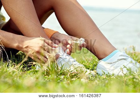 Close-up of female hands tying sports shoes