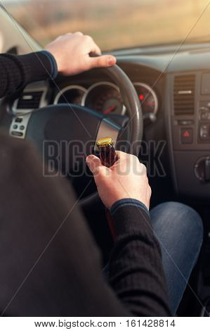 Closeup of man driving a car while drinking alcohol. Transportation safety