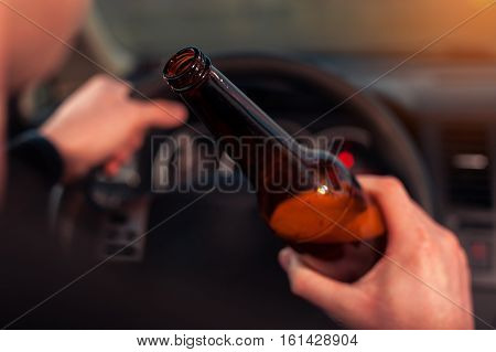 Closeup of male driver hands with steering wheel and beer bottle. Driving under alcohol influence.