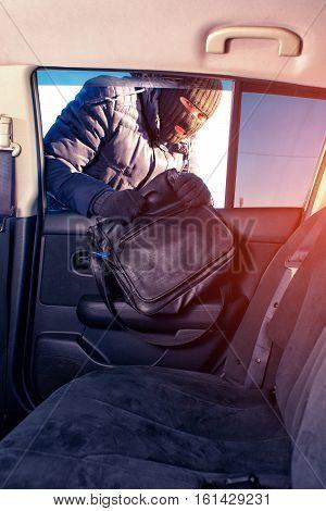 Robber in black balaclava stealing forgotten handbag from opened window.
