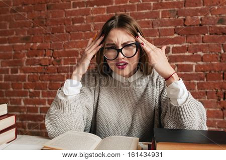 Tired stressed student sitting at desk with books. Attractive woman in glasses having headache because of study. Complicated material, busy schedule, stress concept