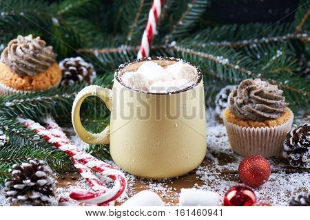 mug with hot chocolate, cup cake, christmas tree, peppermint stick and marshmallow on a snow wooden background. Dark photo.