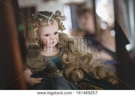Porcelain doll sitting in glass and wood cabinet