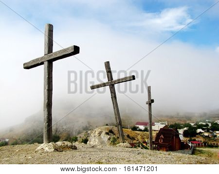 Three crosses on a hill on a background of clouds