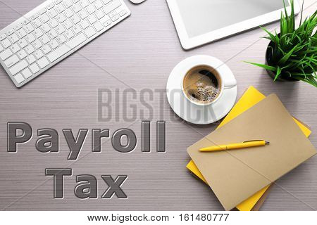 Tax concept. Office workplace, closeup. Text PAYROLL TAX on background