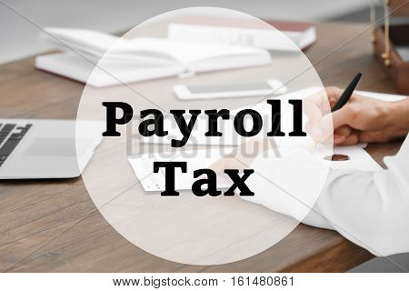 Tax concept. Text PAYROLL TAX on background. Business man at office, closeup