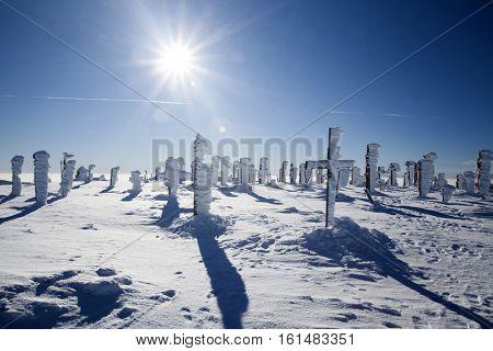 Frozen crosses in winter landscape