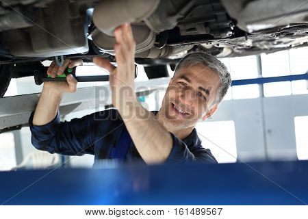 Car repair shop, handsome mechanic at work. Vehicle inspection station, a car for technical inspection. Car repair shop, mechanic repairing a car.