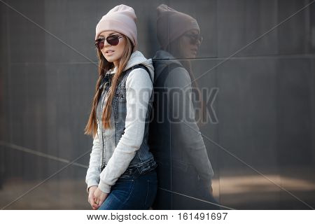 Young beautiful woman with model looks,beautiful makeup,pale pink lipstick,long red hair,wears dark sun glasses,wearing a light knitted sweater and denim vest,blue jeans and a pink sports hat posing on grey background in the city in the fall