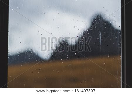 Blurred image of a mountain, which is visible through the rain-spattered window of the house