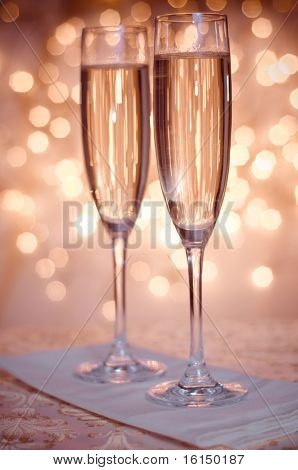 Two champagne glass in yellow abstract background with gold circles