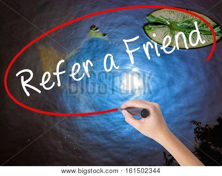 Woman Hand Writing Refer A Friend  With Marker Over Transparent Board