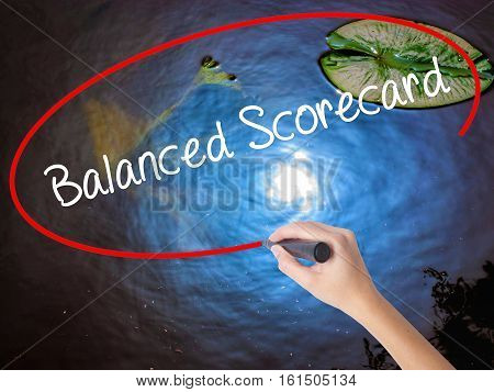 Woman Hand Writing Balanced Scorecard With Marker Over Transparent Board