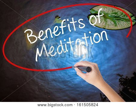 Woman Hand Writing Benefits Of Meditation With Marker Over Transparent Board.