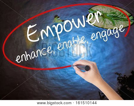 Woman Hand Writing Empower Enhance, Enable, Engage With Marker Over Transparent Board