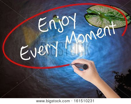 Woman Hand Writing Enjoy Every Moment With Marker Over Transparent Board.