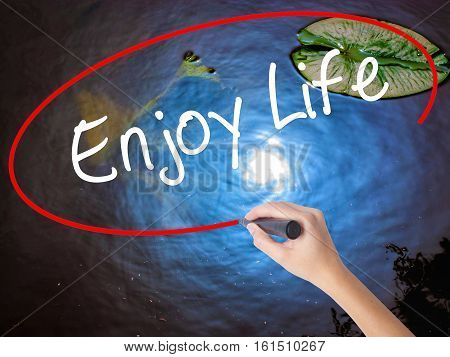 Woman Hand Writing Enjoy Life With Marker Over Transparent Board