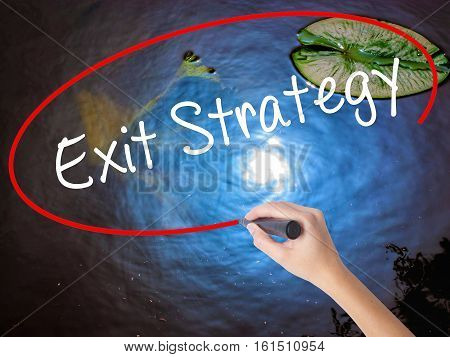 Woman Hand Writing Exit Strategy With Marker Over Transparent Board.