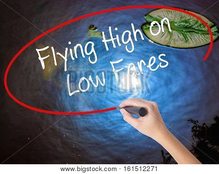 Woman Hand Writing Flying High On Low Fares With Marker Over Transparent Board