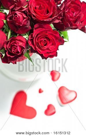 red roses in vase and chocolate candies for Valentine's Day
