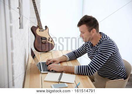 Young composer sitting at a desk with a laptop in light room
