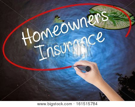 Woman Hand Writing Homeowners Insurance With Marker Over Transparent Board