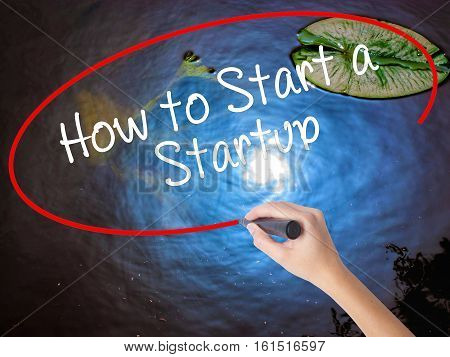 Woman Hand Writing How To Start A Startup With Marker Over Transparent Board