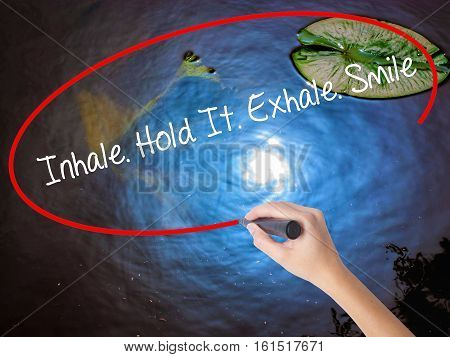 Woman Hand Writing Inhale Hold It Exhale Smile With Marker Over Transparent Board