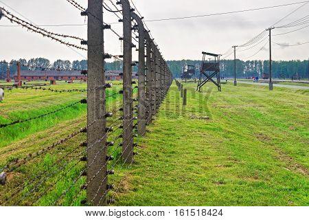 Oswiecim, Poland - May 2, 2014: Razor wire and Watch tower in concentration camp Auschwitz Birkenau Poland.