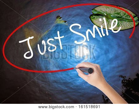Woman Hand Writing Just Smile With Marker Over Transparent Board
