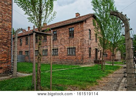 Oswiecim, Poland - May 2, 2014: Razor wire and barracks at Auschwitz concentration camp Poland.