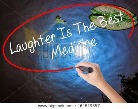 Woman Hand Writing Laughter Is The Best Medicine  With Marker Over Transparent Board