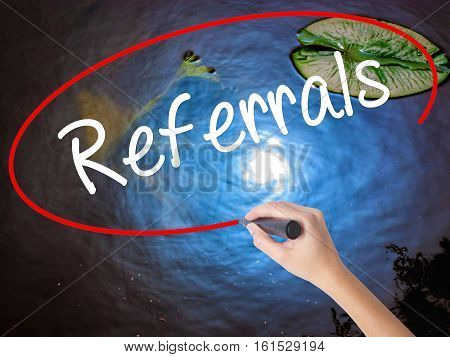 Woman Hand Writing Referrals With Marker Over Transparent Board.