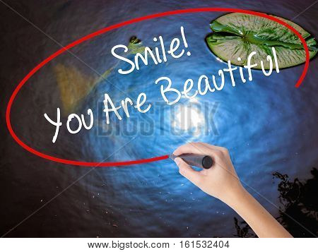 Woman Hand Writing Smile! You Are Beautiful With Marker Over Transparent Board
