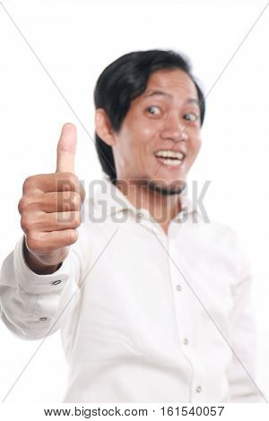 Photo image portrait of a cute funny young Asian man showing thumb up gesture with smiling face close up portrait over white background focus on hand with blur face