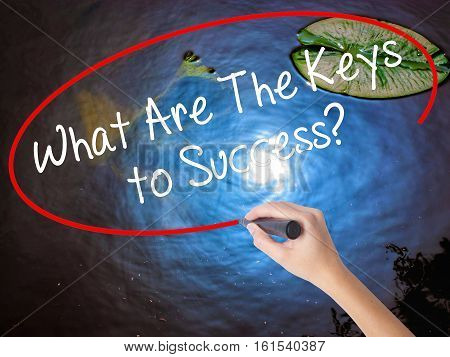Woman Hand Writing What Are The Keys To Success? With Marker Over Transparent Board