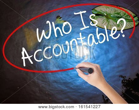 Woman Hand Writing Who Is Accountable? With Marker Over Transparent Board
