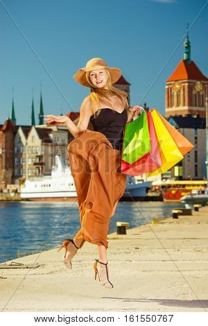 Fashionable Woman Jumping With Shopping Bags