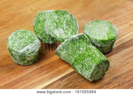 Group of frozen spinach food briquette blocks on wooden background