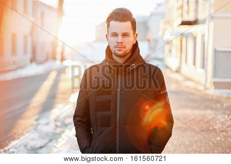 Handsome Young Man With Hair Style In A Black Jacket Walking On The Street At Sunset
