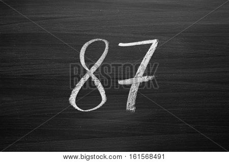 number eighty seven enumeration written with a chalk on the blackboard