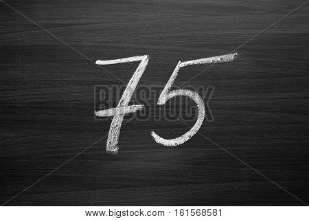 number seventy five enumeration written with a chalk on the blackboard