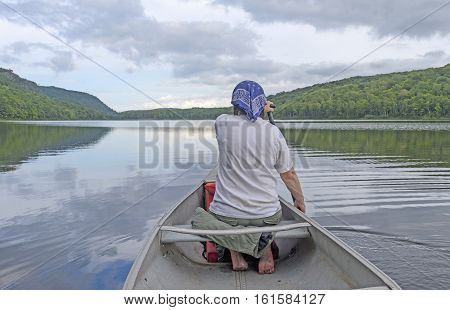 Barefoot Paddler on a Calm Lake on Lake of the Clouds in Porcupine Mountains State Park in Michigan