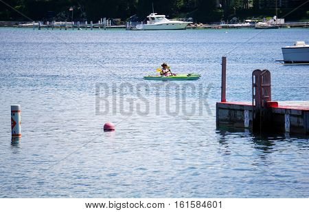 HARBOR SPRINGS, MICHIGAN / UNITED STATES - AUGUST 3, 2016: Kayaks are paddled near the Zorn Park Public Beach near downtown Harbor Springs.