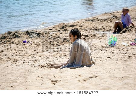 HARBOR SPRINGS, MICHIGAN / UNITED STATES - AUGUST 3, 2016: A girl sits in the sand at the Zorn Park Public Beach near downtown Harbor Springs.