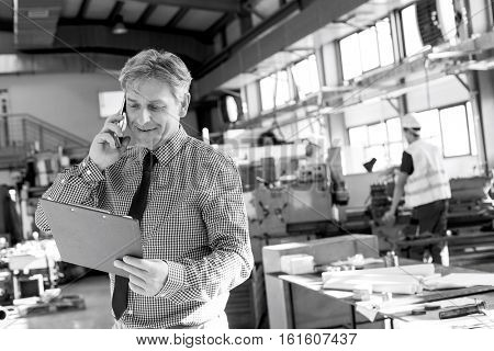 Mature male supervisor looking at clipboard while talking on mobile phone in industry