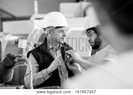 Male inspector having discussion with worker in metal industry