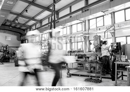 Blurred motion of business people walking with manual worker in background at industry